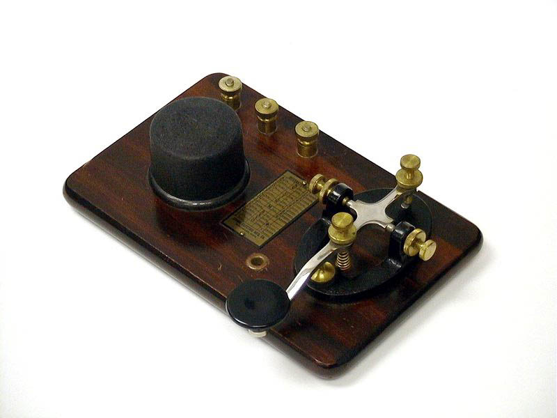 <b>Signal KOB</b> (1945) : Figure 57 : Telegraph Key and Buzzer on base. Brass hardware, steel lever key with black cast iron base mounted on a wooden base with a round black buzzer. Morse Code brass plate. Wiring diagram on the bottom. :